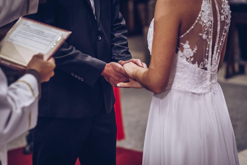novios tomados de la mano en ceremonia por la Iglesia
