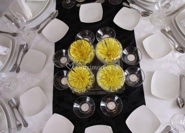 Centro de mesa con velas y flores amarillas