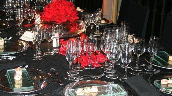 Mesa con platos plateados y de vidrio