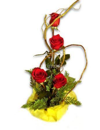 Arreglo floral con ramas silvestres y rosas
