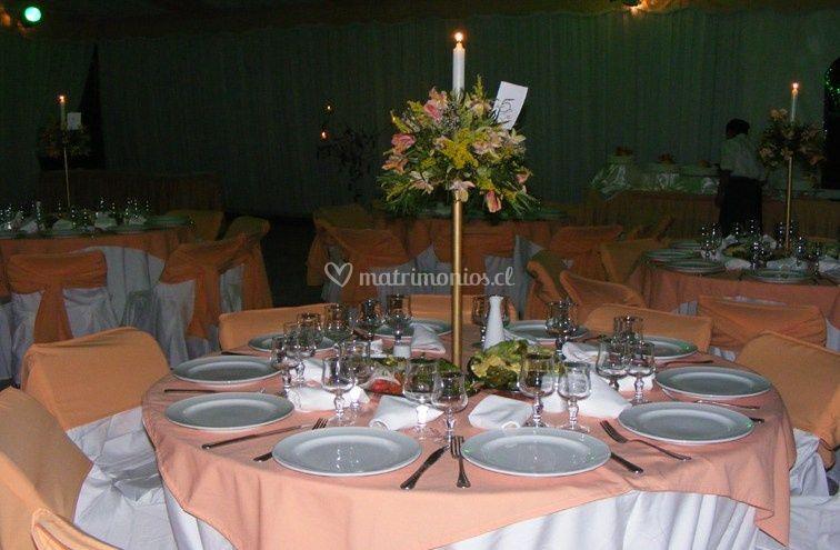Mesa con mantel rosa y arreglo floral con vela