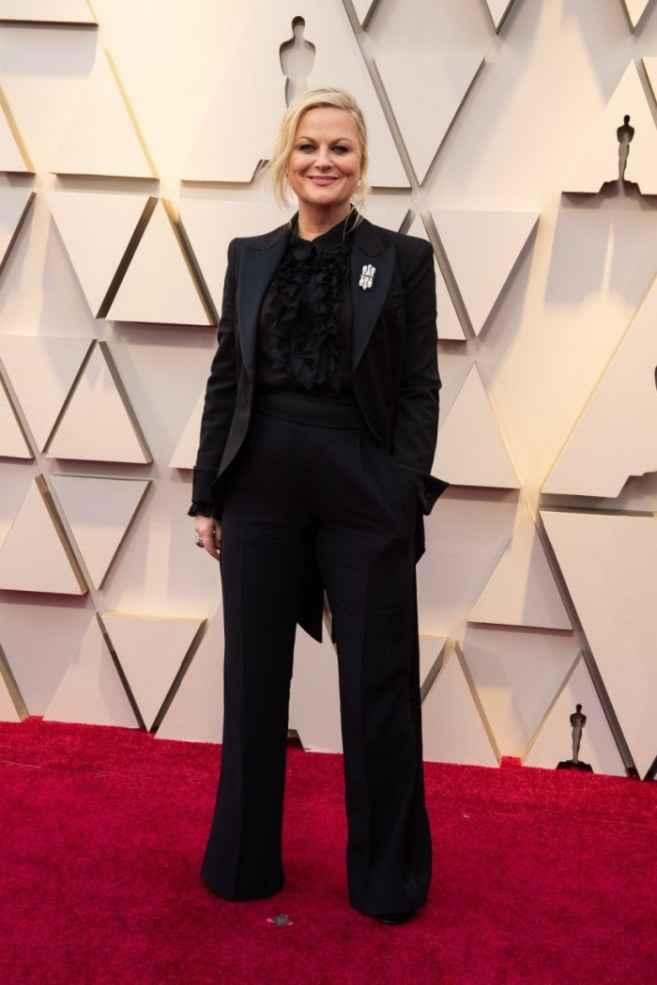 18. Amy Poehler con un look muy original de traje negro y camisa con chorreras a juego de Alberta Fe